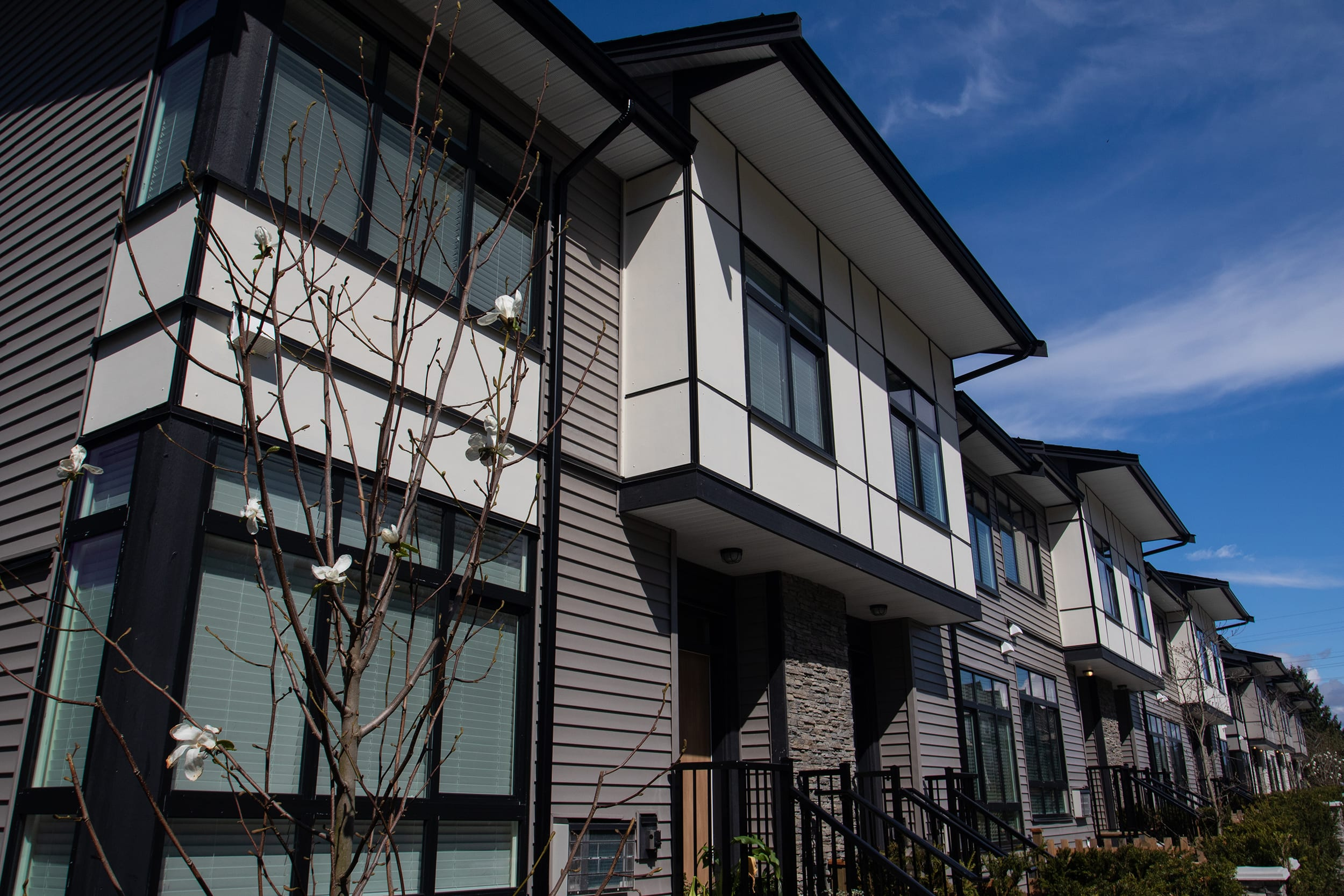 A modern townhome complex features black window trim and multiple building materials, including siding and rock, to create an interesting streetscape.