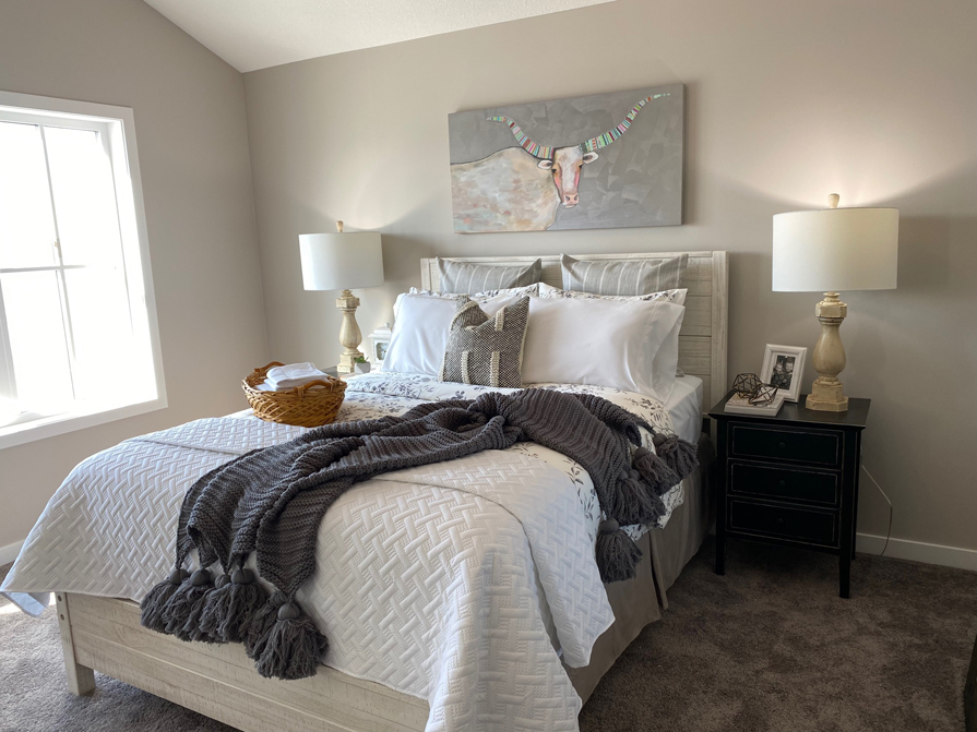 Showhome bedroom with light grey wall paint, grey wood bedframe and white linens