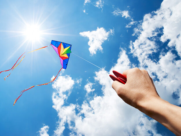 A colorful kite being flown in a blue sky with white clouds.