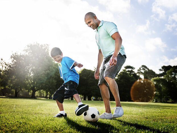 A father and son kick a soccer ball on green grass.