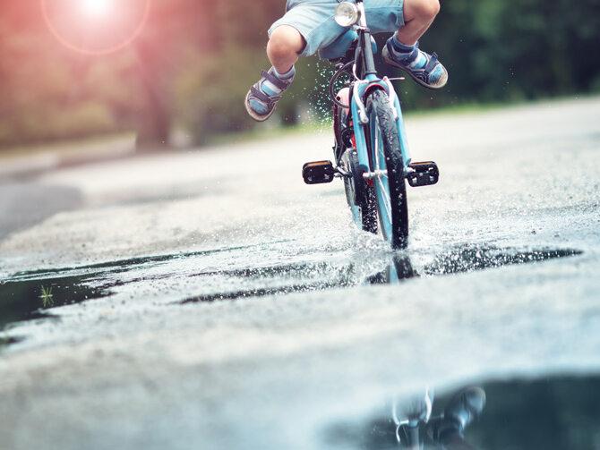 A child rides its bike through a rain puddle.