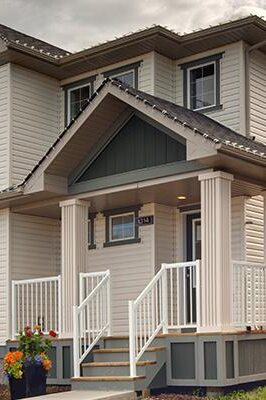 A modern prairie laned home with detached garage features grey window trim, light grey siding and including a wide front porch.
