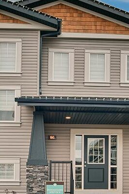 A modern prairie laned home with detached garage features light grey window trim, grey siding with wood and rock detail, including a wide front porch.